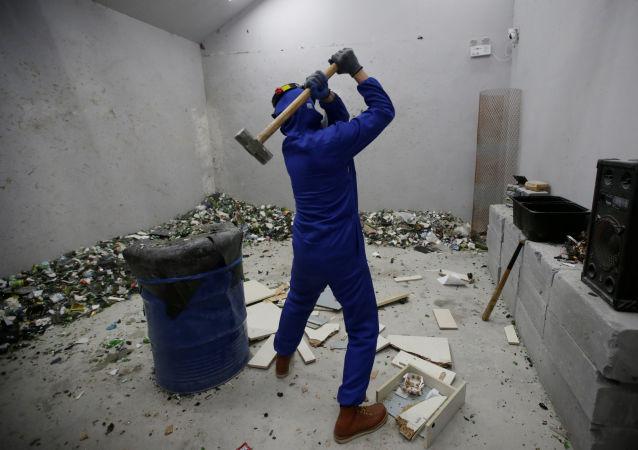 غرفة الغضب في بكين - أحد الزوار يحطم قطعة أثاث بواسطة شاكوش، الصين 12 يناير/ كانون الثاني 2019