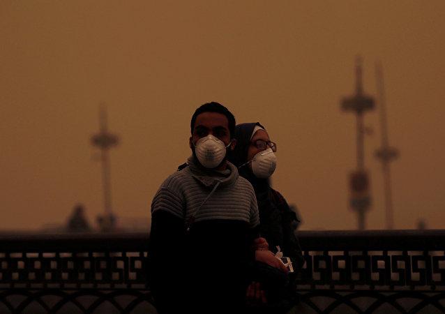 زوجان يغطيان وجهيهما بأقنعة أثناء عاصفة رملية في القاهرة