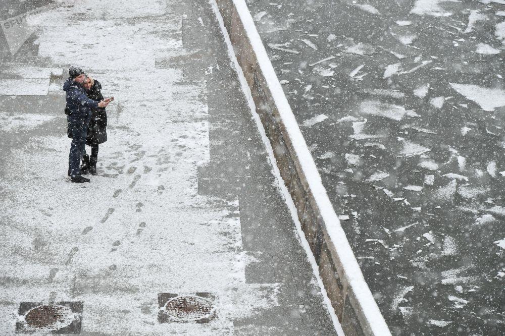 شخصان يلتقطان صورة سيلفي على خلفية تساقط ثلوج كثيف على ضفة نهر موسكو