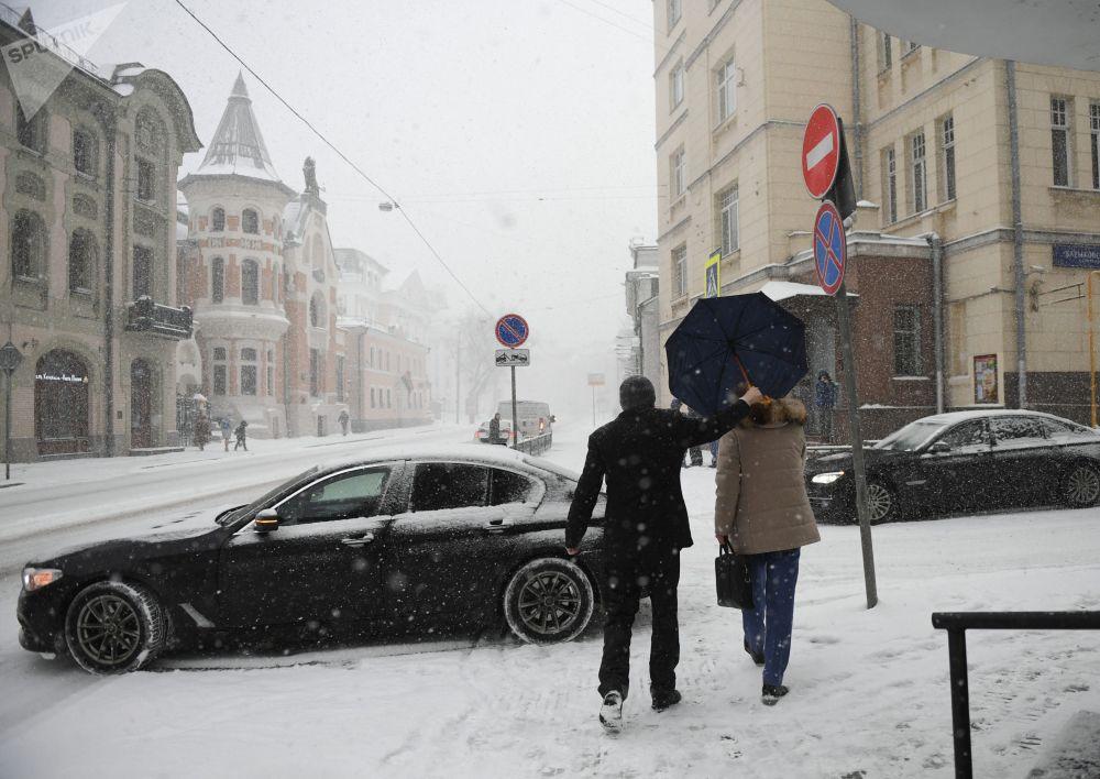 أحد المارة في شارع أوستوجينكا خلال تساقط ثلوج كثيفة في موسكو