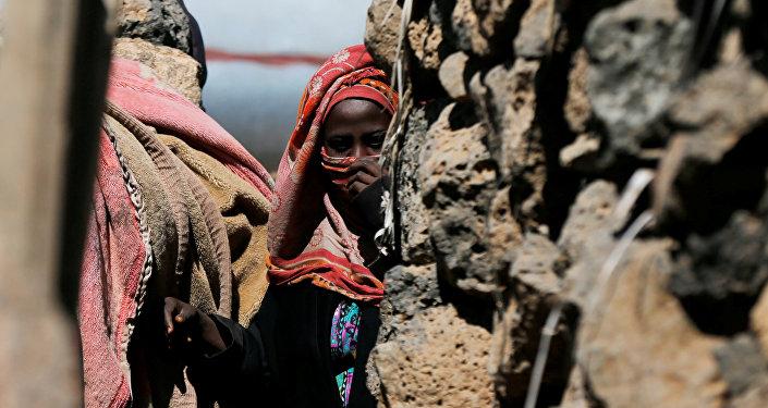 امرأة تقف بالقرب من كوخها في مخيم مؤقت للنازحين قرب صنعاء