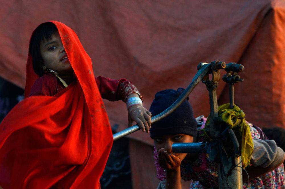 طفلة غجرية باكستانية تشرب الماء من مضخة يدوية في لاهور، باكستان 27 يناير/ كانون الثاني 2019