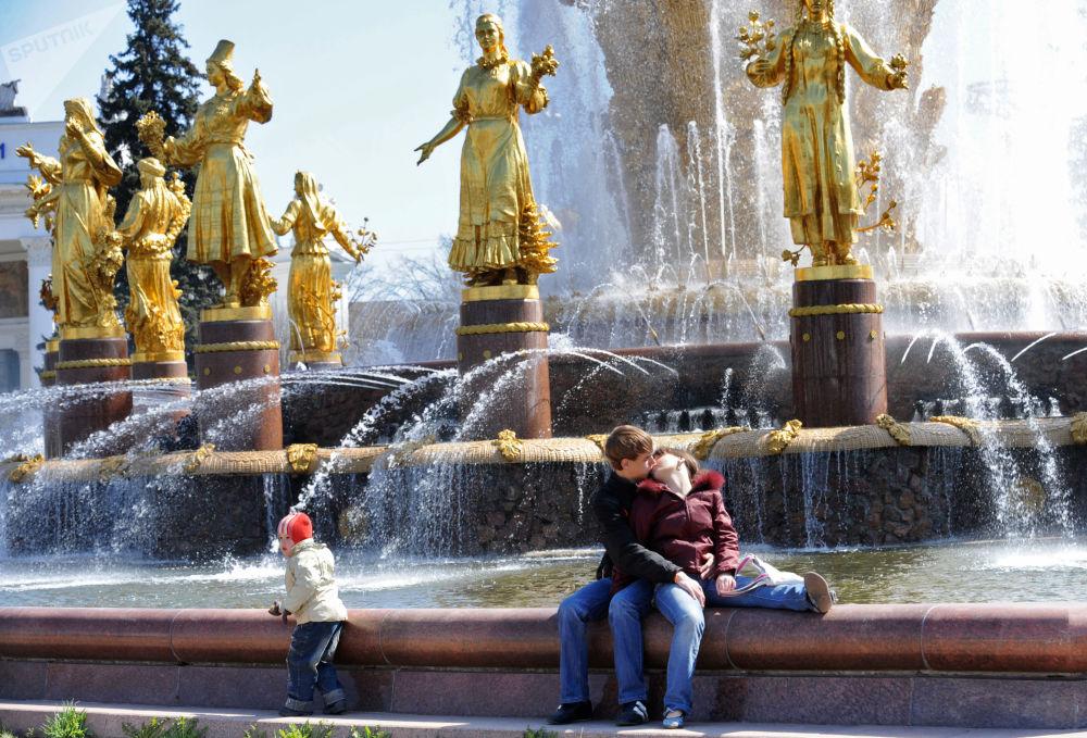 شخصان يجلسان على نافورة دروجبا نارودوف (صداقة الشعوب) في حديقة في دي إن خا موسكو