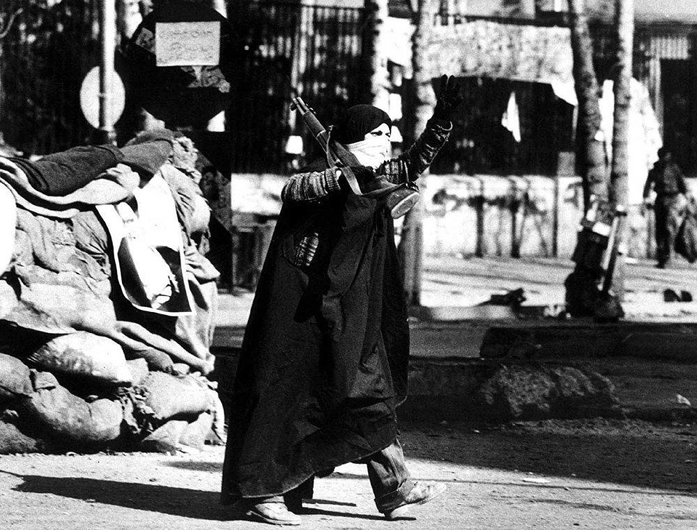 امرأة إيرانية تلوح بعلامة النصر وهي تحمل بندقية في طهران أثناء ثورة البلاد في فبراير/ شباط 1979