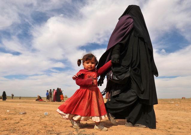 امرأة منقبة، لاجئة، تسير مع طفلتها يخلون منطقة باغوز، خلال عملية قامت بها القوات الديمقراطية السورية المدعومة من الولايات المتحدة لطرد تنظيم داعش الإرهابي من المنطقة، في محافظة دير الزور السورية الشرقية، سوريا 13 فبراير/ شباط 2019