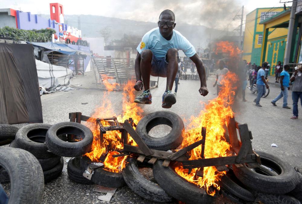 متظاهر يقفز فوق حاجز محترق أثناء احتجاجات ضد الحكومة في شوارع بورت أو برنس، هايتي، 10 فبراير/ شباط 2019
