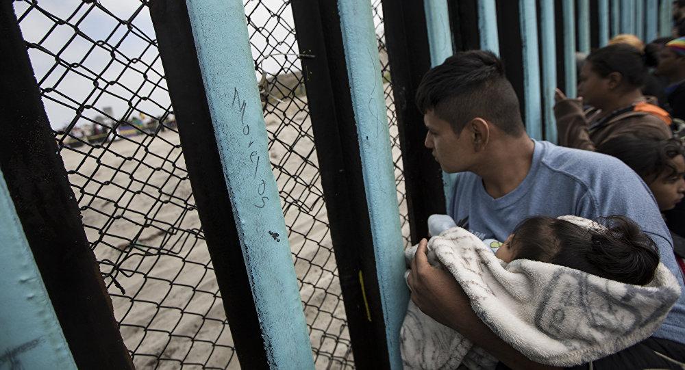 مهاجر يحمل ولده على الحدود بين المكسيك وأمريكا
