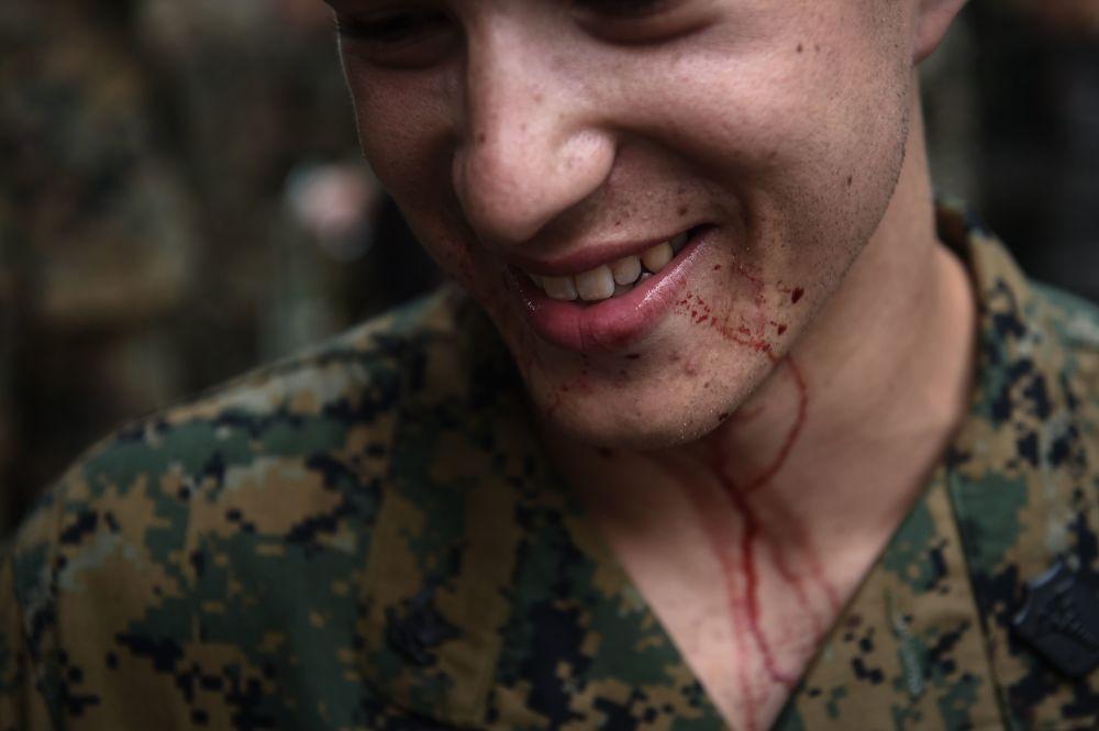 ابتسامة أحد مشاة البحرية الأمريكية بعد الشرب من دماء أفعى الكوبرا، خلال التدريبات العسكرية المشتركة كوبرا غولد (Cobra Gold) في مقاطعة تشونبوري الساحلية في 19 فبراير/ شباط 2018.