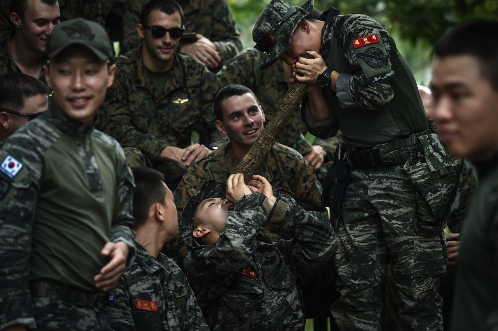 مشاة البحرية الأمريكية يشاهدون مشاة البرحية الكوري الجنوبي يستخرجون الماء من الكرمة، خلال التدريبات العسكرية المشتركة كوبرا غولد (Cobra Gold) في مقاطعة تشونبوري الساحلية في 19 فبراير/ شباط 2018.