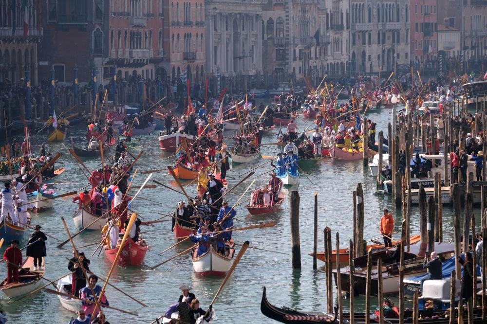 تتحرك القوارب المزخرفة على القنال الكبير (القناة الكبيرة) بالقرب من كنيسة سانتا ماريا ديلا سالوت، خلال افتتاح سباق الزوارق لكرنفال فينيسيا، البندقية، 17 فبراير/ شباط 2019