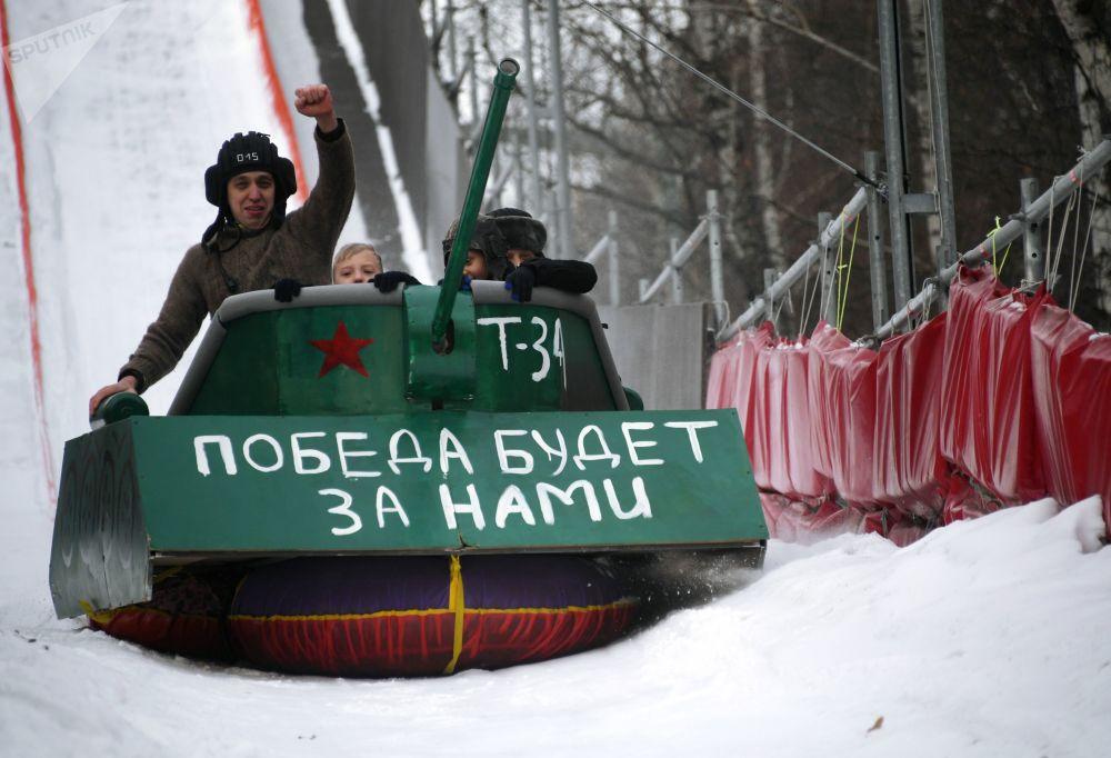 يتدفق المشاركون في مهرجان سباق الزلاجات غير العادية باتل ساني (Battle сани)، على تل يبلغ طوله 200 متر، في حديقة سوكولنيكي في موسكو. المهرجان مخصص للاحتفال بيوم حماة الوطن