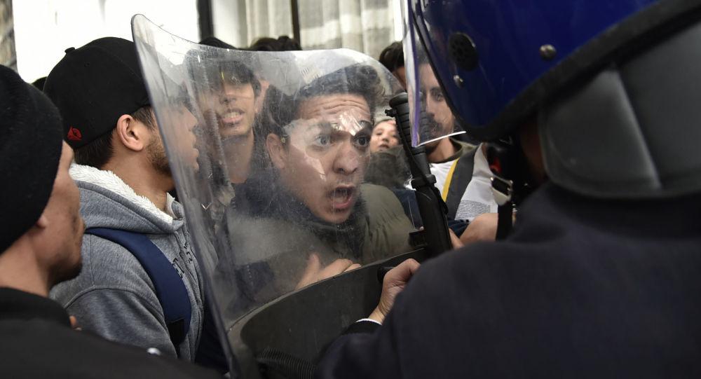طلاب جزائريون يشتبكون مع قوات حفظ الأمن خلال مظاهرة في العاصمة الجزائر، وذلك خلال احتجاجات على محاولة الرئيس الجزائري المريض عبد العزيز بوتفليقة لولاية خامسة في 26 فبراير/ شباط 2019.