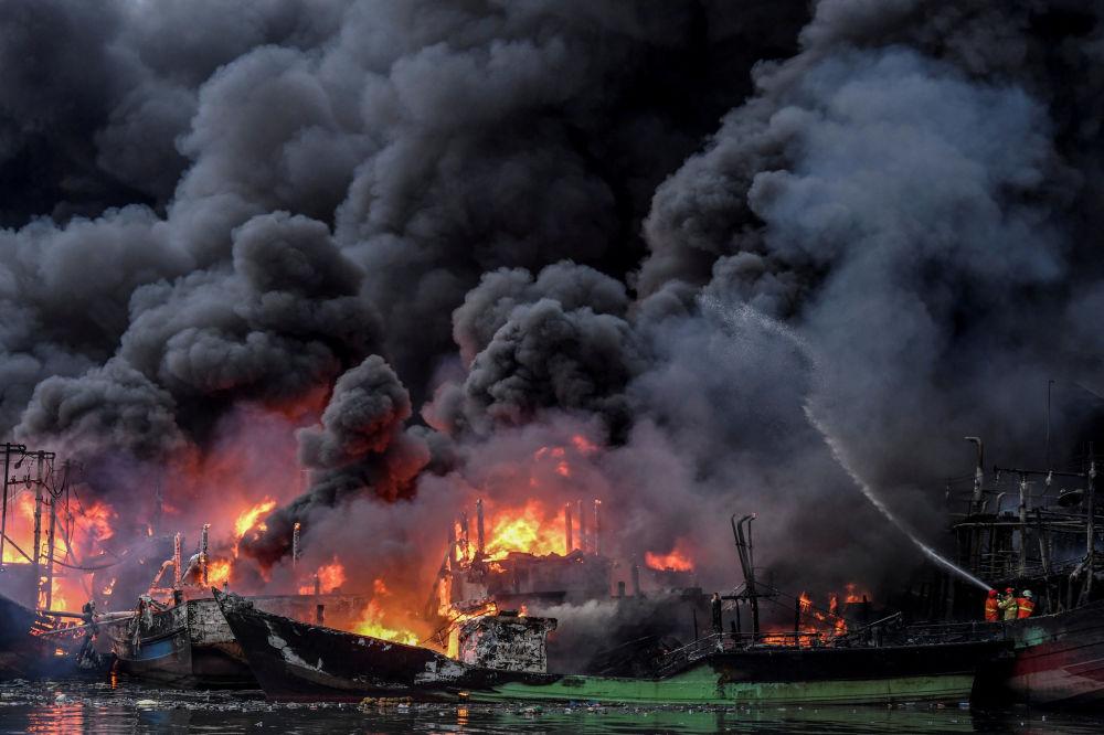رجال الإطفاء يحاولون إطفاء قوارب الصيد التي اشتعلت فيها النيران في ميناء موارا بارو في جاكرتا، إندونيسيا ، 23 فبراير/ شباط 2019