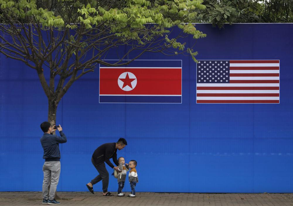 مواطنون يلتقطون صورة على خلفية علمي كوريا الشمالية والولايات المتحدة الأمريكية، في ظل القمة الأمريكية الكورية في هانوي، فيتنام 27 فبراير/ شباط 2019
