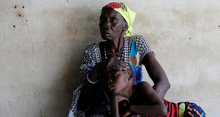 امرأة ترافق ابنها الذي يعاني من الملاريا أثناء انتظار العلاج في عيادة تديرها منظمة أطباء بلا حدود في قرية ليكوانغول في ولاية بوما شرق جنوب السودان