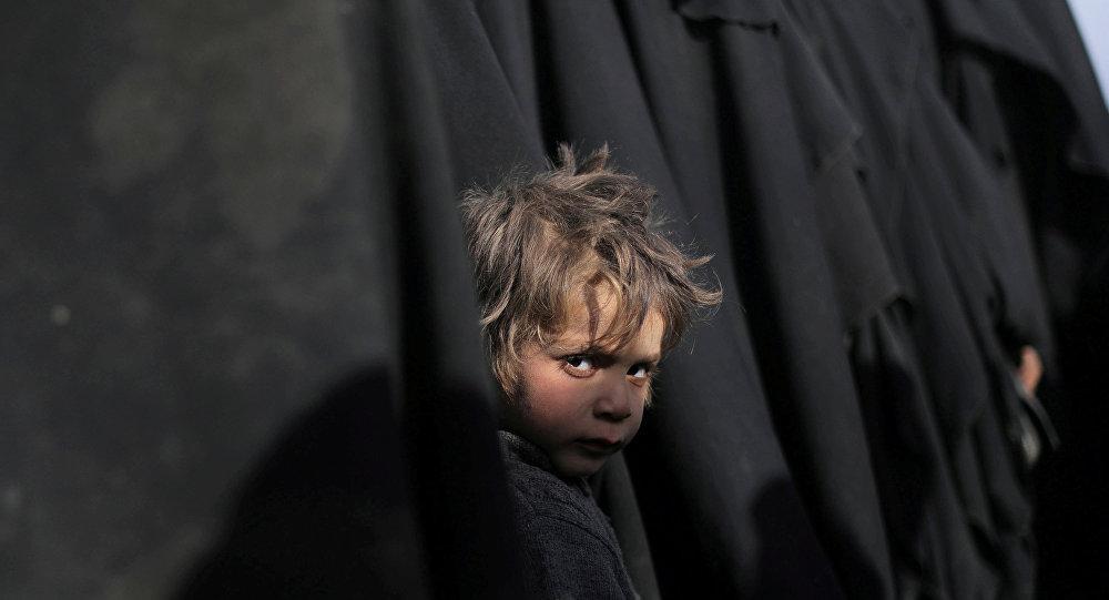 صبي ينظر إلى الكاميرا بالقرب من الباغوز محافظة دير الزور في سوريا