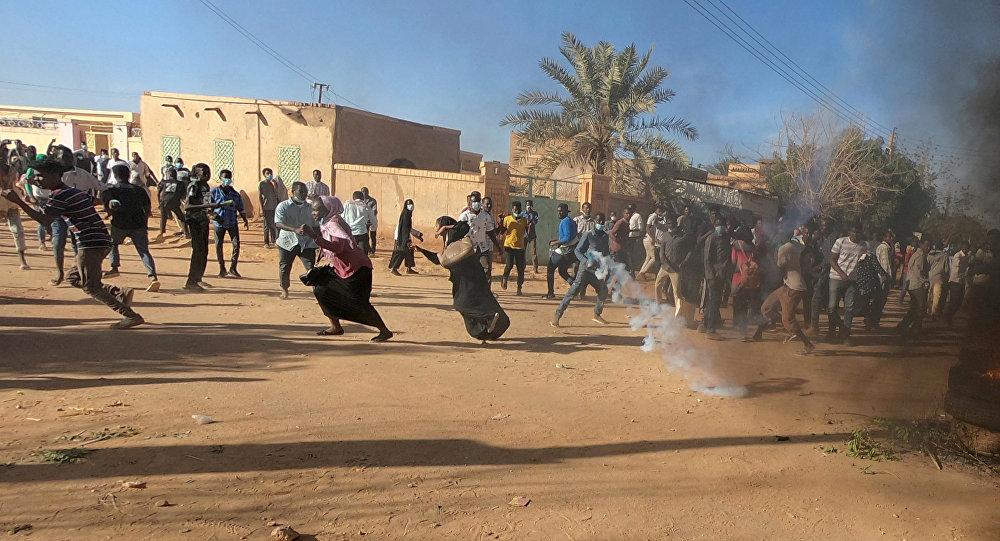 متظاهرون سودانيون يركضون من عبوة غاز مسيل للدموع أطلقها رجال شرطة مكافحة الشغب لتفريقهم وهم يشاركون في مظاهرات مناهضة للحكومة في أم درمان بالخرطوم