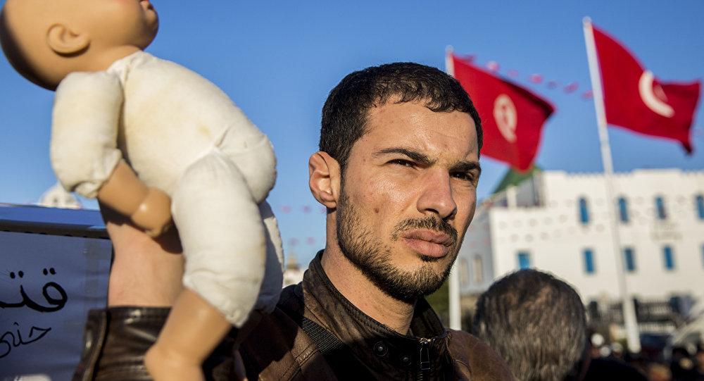 متظاهر في تونس يحمل دمية لطفل للتنديد بوفاة أطفال رضع في مستشفى حكومي