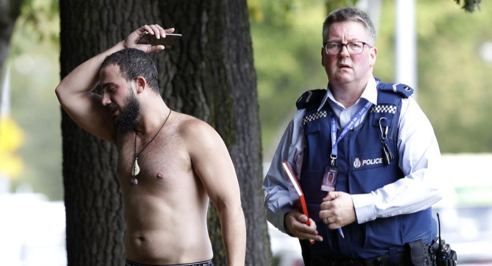 رجل وشرطي في مكان الهجوم الإرهابي على مسجد النور في نيوزيلاندا