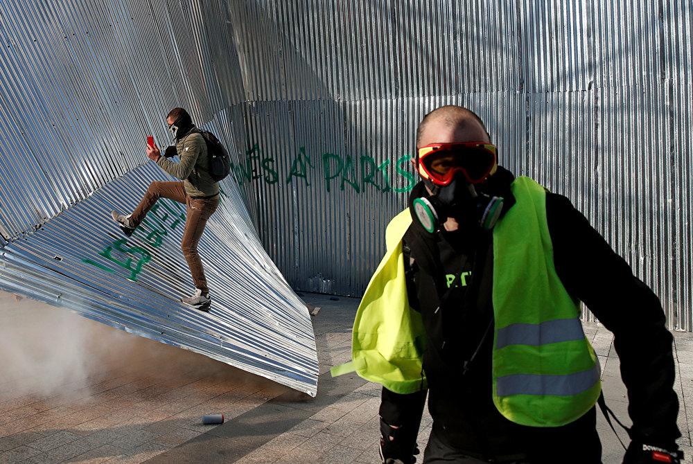 متظاهر يرتدي سترة صفراء يمشي أمام سياج معدني هدم أثناء مظاهرة من قبل حركة السترات الصفراء في باريس