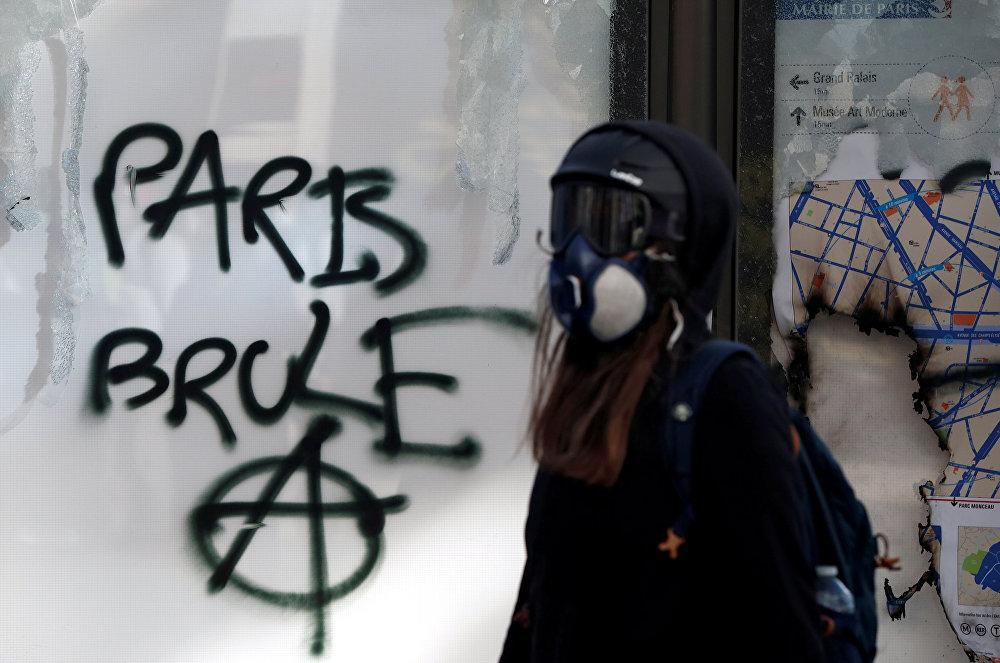 متظاهرة أمام كتابات على الجدران أثناء مظاهرة من قبل حركة السترات الصفراء في باريس