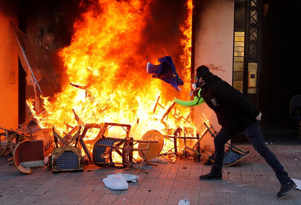 متظاهر يلقي علم الاتحاد الأوروبي بنيران متجر محترق أثناء مظاهرة من قبل حركة السترات الصفراء في باريس