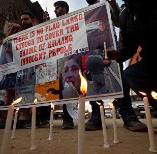 يضيء الناس الشموع وهم يحملون لافتة خلال احتجاج على هجمات مسجد الجمعة في نيوزيلندا