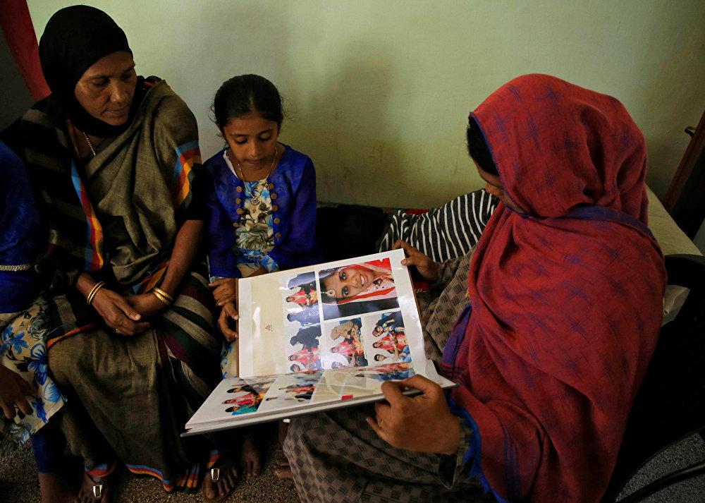 أقارب وجيران ينظرون إلى ألبوم زفاف أنسي علي بافا الذي قُتل في هجمات مسجد الجمعة في نيوزيلندا في منزل والديها في كودونغالور