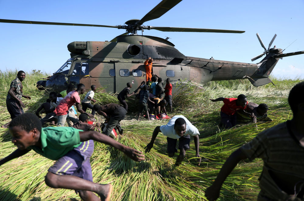 سكان محليون يركضون باتجاه طائرة هليكوبتر تابعة لجيش الدفاع الوطني لجنوب إفريقيا، التي نقلت المساعدات الغذائية إلى القرية المتضررة من الإعصار أيداي، موزمبيق 26 مارس/ آذار 2019