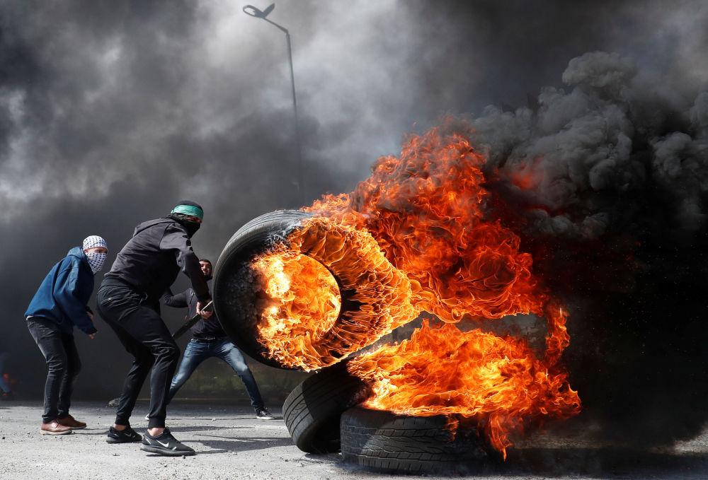 متظاهرون فلسطينيون وإطارات مشتعلة خلال اشتباكات مع القوات الإسرائيلية بالقرب من مستوطنة بيت إيل في الضفة الغربية، 27 مارس/ آذار 2019