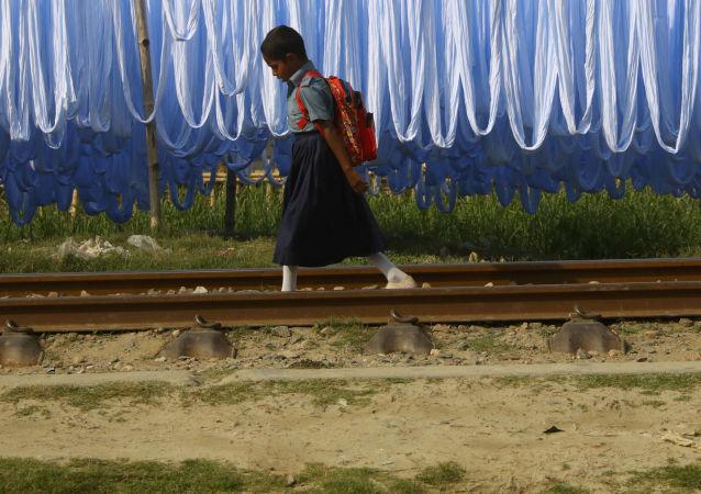تلميذة تسير على السكة الحديدية في نارايانغانج، بنغلاديش 25 مارس/ آذار 2019