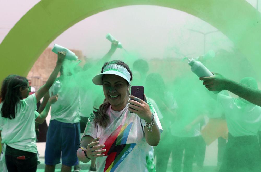متطوعون يصبون اللون الأخضر على الحاصلين على المركز الثالث في أول مسابقة الألوان في الجيزة، مصر في 13 أبريل/ نيسان 2019