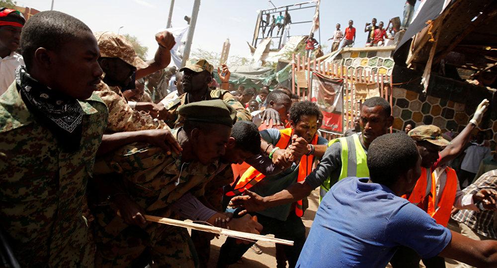 متظاهرون سودانيون يضربون رجلا يعتقد أنه عميل حكومي بينما يحاول الجنود إخراجه من الحشد في الخرطوم