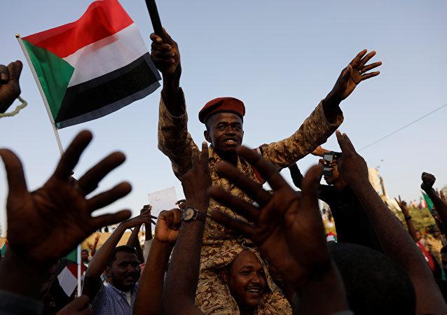 جندي سوداني يجلس على أكتاف أحد المتظاهرين وهو يهتف مع الحشد خارج وزارة الدفاع في الخرطوم