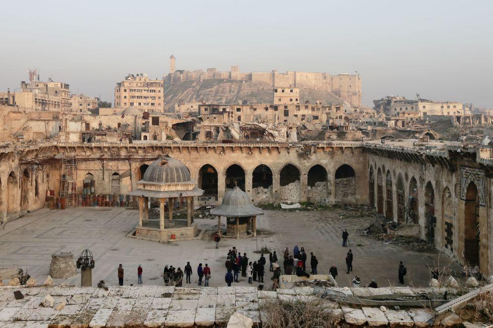 دمار كبير يلحق بجامع حلب الكبير، على خلفية قلعة حلب (القرن الـ13)، في البلدة القديمة في حلب، عام 2017