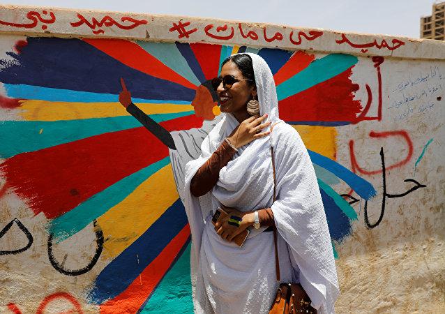 آلاء صلاح تقف أمام لوحة جدارية تصورها أمام وزارة الدفاع في الخرطوم