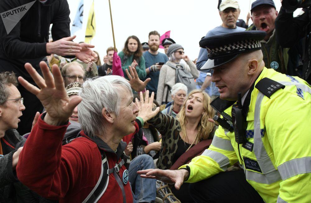 ضابط شرطة يتواصل مع أحد المشاركين في احتجاجات ضد التلوث البيئي في أحد شوارع لندن