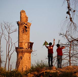 فتيان يلعبون بالقرب من مسجد تاريخي مدمر في حلب