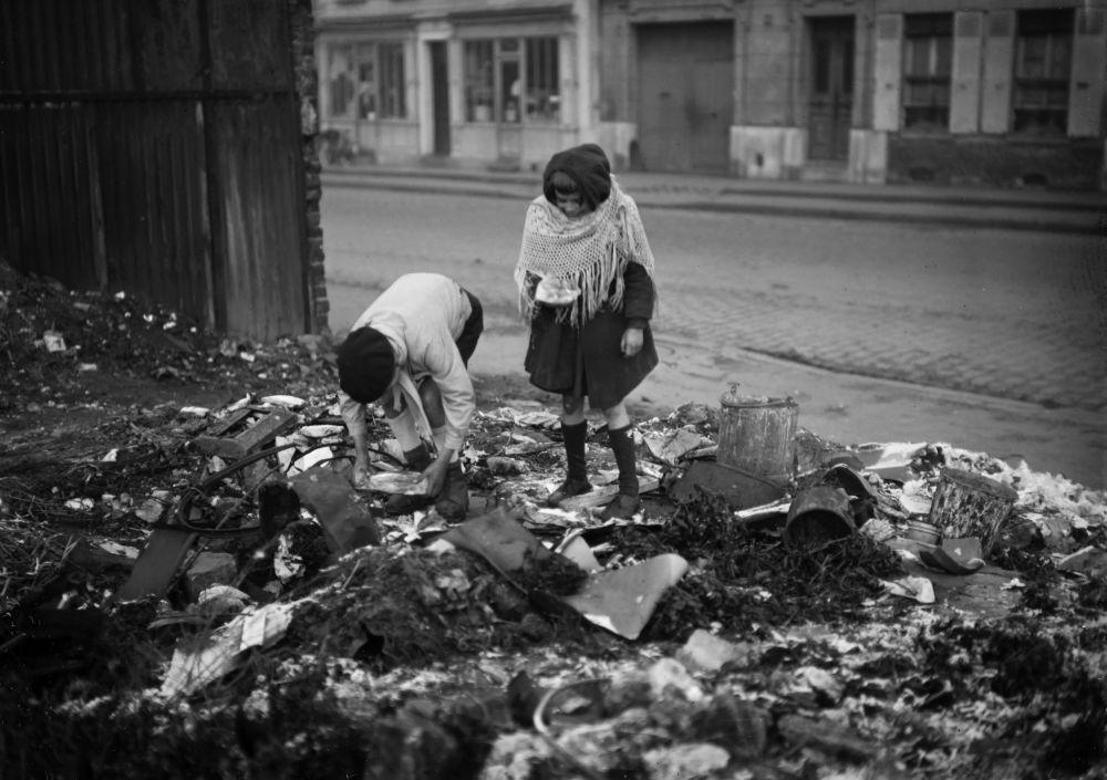 أطفال يفتشون القمامة في أحد شوارع باريس خلال الحرب العالمية الثانية، عام 1945