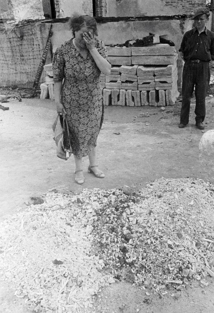 امرأة تبكي على رماد الأشخاص المحروقين في أفران معسكر الموت النازي في لوبلان، بولندا، عام 1944