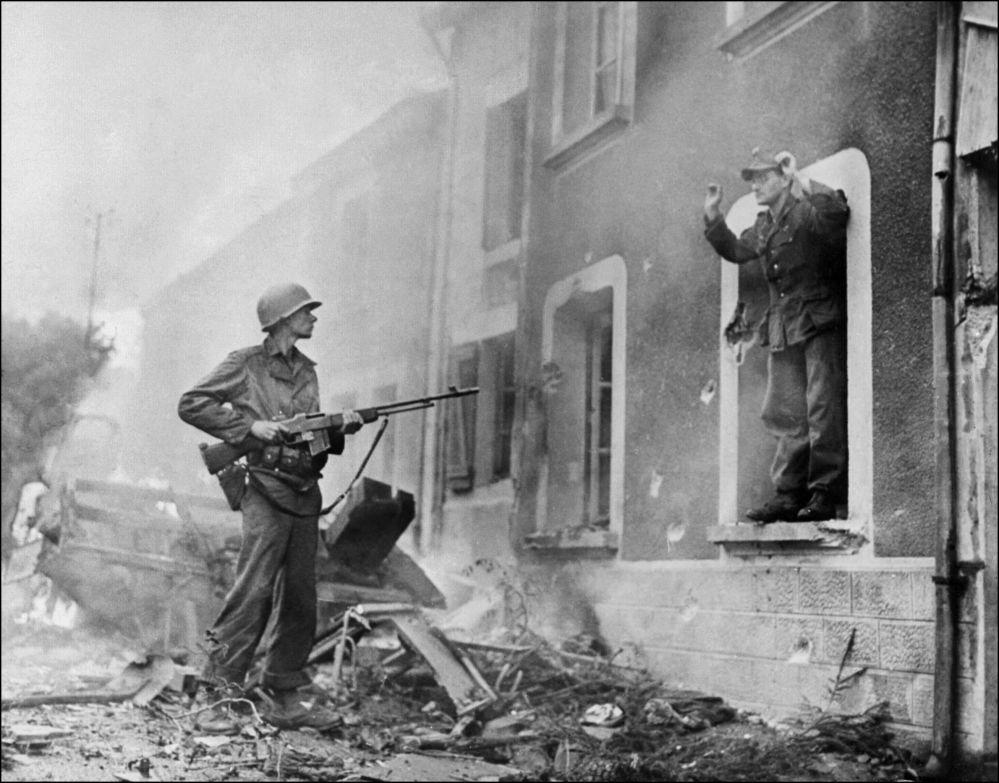 جندي أمريكي يوجه بندقيته نحو جندي ألماني أثناء تحرير فرنسا، عام 1944