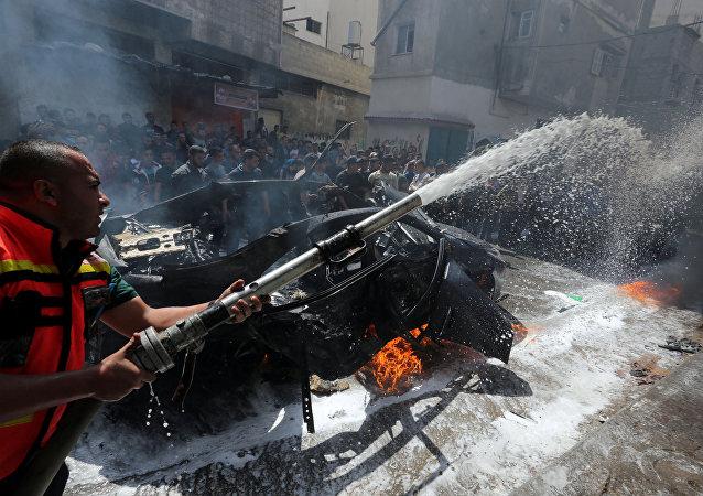 عضو في الدفاع المدني الفلسطيني يطفئ حريقا في سيارة القيادي الحمساوي حامد أحمد عبد الخضري الذي قتل في غارة جوية إسرائيلية في مدينة غزة