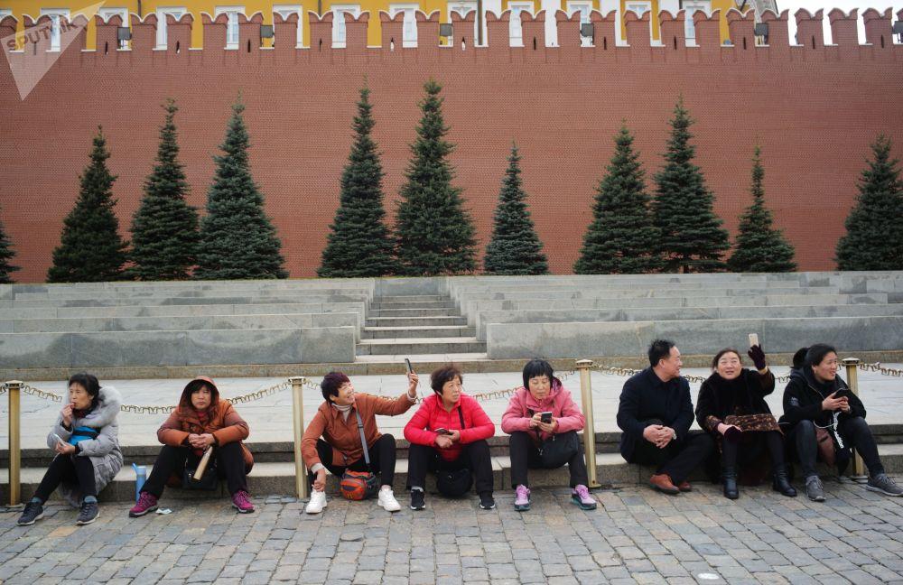 سياح يلتقطون صورة سيلفي على خلففية سور الكرملين