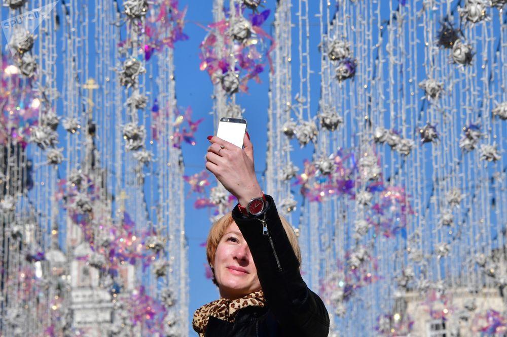 امرأة تلتقط صورة على خلفية أضواء شارع نيكولسكايا في موسكو