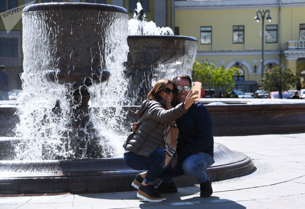 سياح يلتقطون صورة سيلفي على خلفية نافورة المسرح الكبير في موسكو