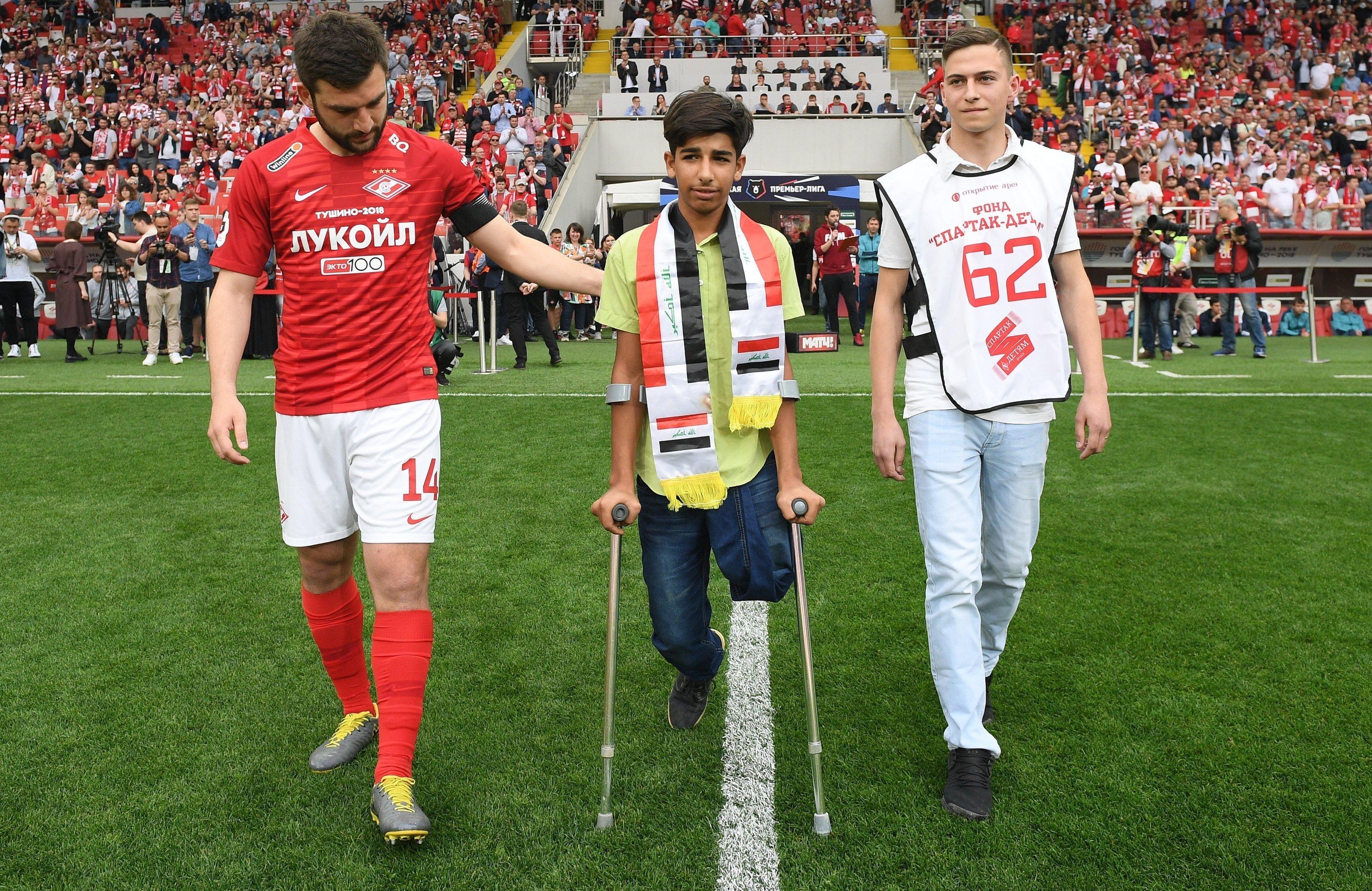 الفتى العراقي بطل صورة الرغبةفي الحياة يركل كرة البداية في مباراة بالدوري الروسي