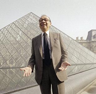 المهندس المعماري آي. إم. بي أمام تحفته أهرامات اللوفر
