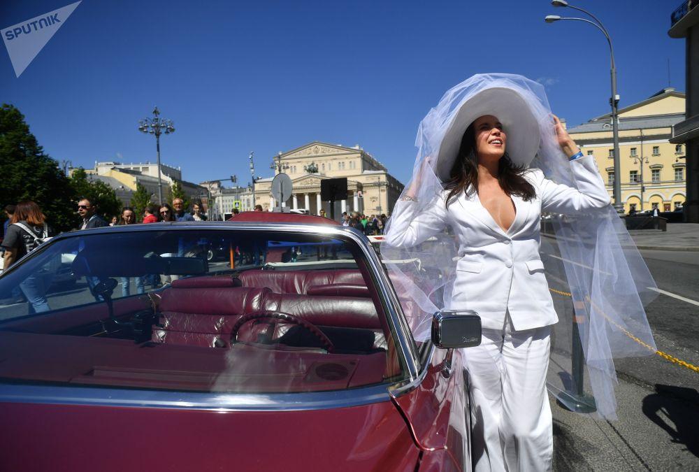 فتاة تقف أماملسيارة كاديلاك الدورادو، 1978  (Cadillac Eldorado 1978) في رالي السيارات الكلاسيكية القديمة في موسكو