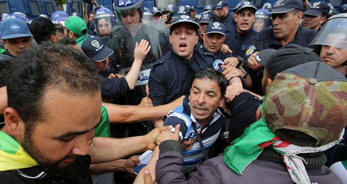 يواجه المتظاهرون وضباط الشرطة بعضهم البعض خلال احتجاج للمطالبة بتأجيل الانتخابات الرئاسية في الجزائر العاصمة