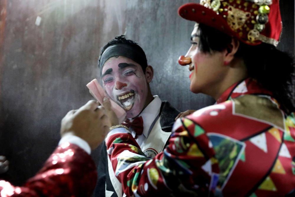 مهرجون يستعدون  للمشاركة في عرض أثناء احتفالات يوم المهرج في بيرو في ليما، بيرو، 25 مايو/ أيار 2019